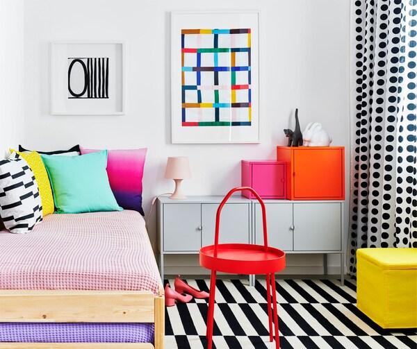 Chambre affichant des couleurs uniformes et des motifs. Lit accueillant des coussins, et armoires EKET.