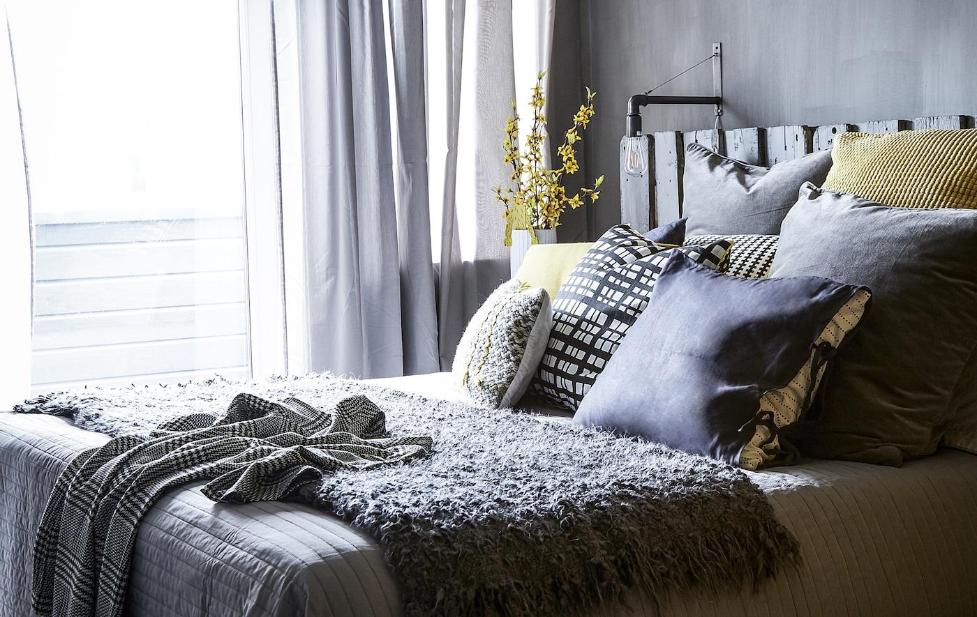 Chambre avec déco grise et coussins jaunes.