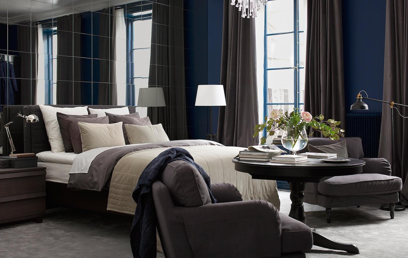 Chambre avec mur de miroirs, lit garni de nombreux textiles, fauteuil, lampadaires et fleurs coupées.