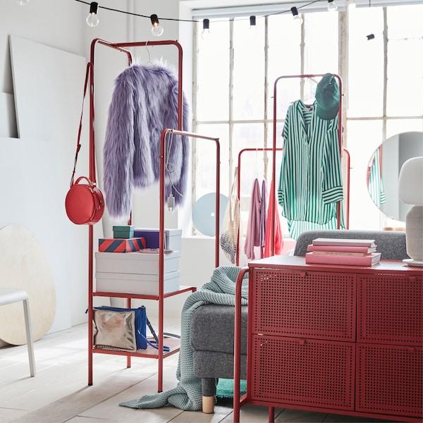 Chambre colorée avec deux portants rouges chargés de vêtements ainsi que de boîtes de rangement sur les tablettes du bas.