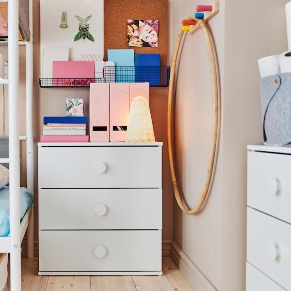 Chambre d'enfant avec applique blanche et deux commodes blanches sur lesquelles sont posés des livres et des range-revues.