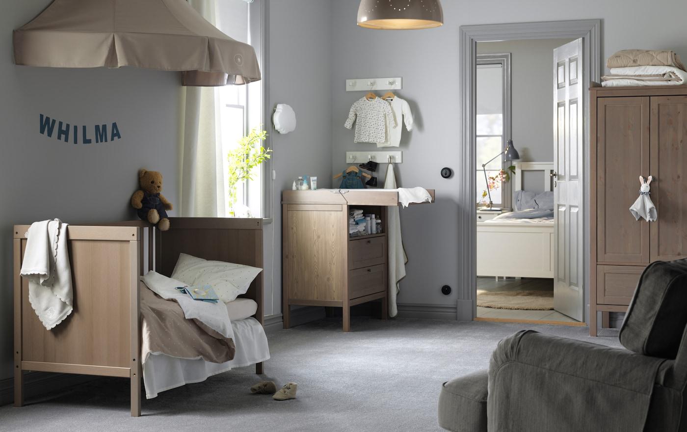 Chambre d'enfant avec lit bébé gris-brun transformé en lit pour enfant et ciel de lit beige. Dans le fond une table à langer et une armoire gris-brun.