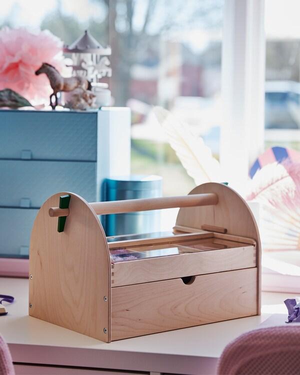 Chambre d'enfant – gros plan sur une boîte contenant des fournitures pour loisirs créatifs, posée sur un bureau blanc devant une boîte décorative.