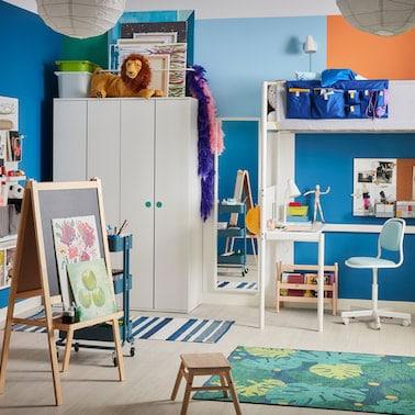 Chambre d'enfant multicolore avec lit mezzanine blanc, chevalet, tapis à motifs de feuilles et chaise de bureau enfant bleue.