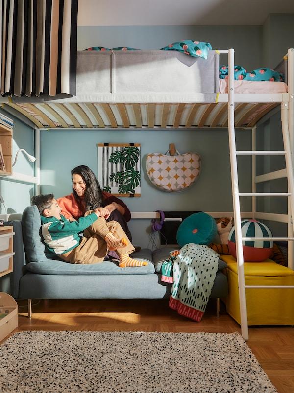 Chambre d'enfant où une femme et un garçon sont assis ensemble dans le coin-détente confortable aménagé sous un lit mezzanine blanc VITVAL.
