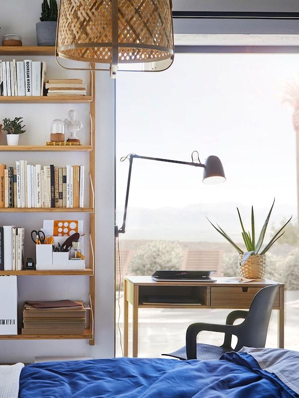 Chambre ensoleillée avec bureau en bambou près de la fenêtre.