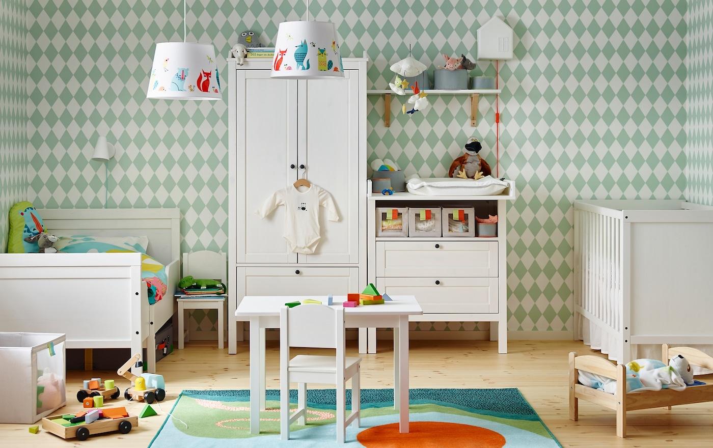 Chambre partagée avec table à langer SUNDVIK qui se convertit en table à langer, lit bébé SUNDVIK et lit extensible SUNDVIK contre un mur à losanges vert clair et blanc.
