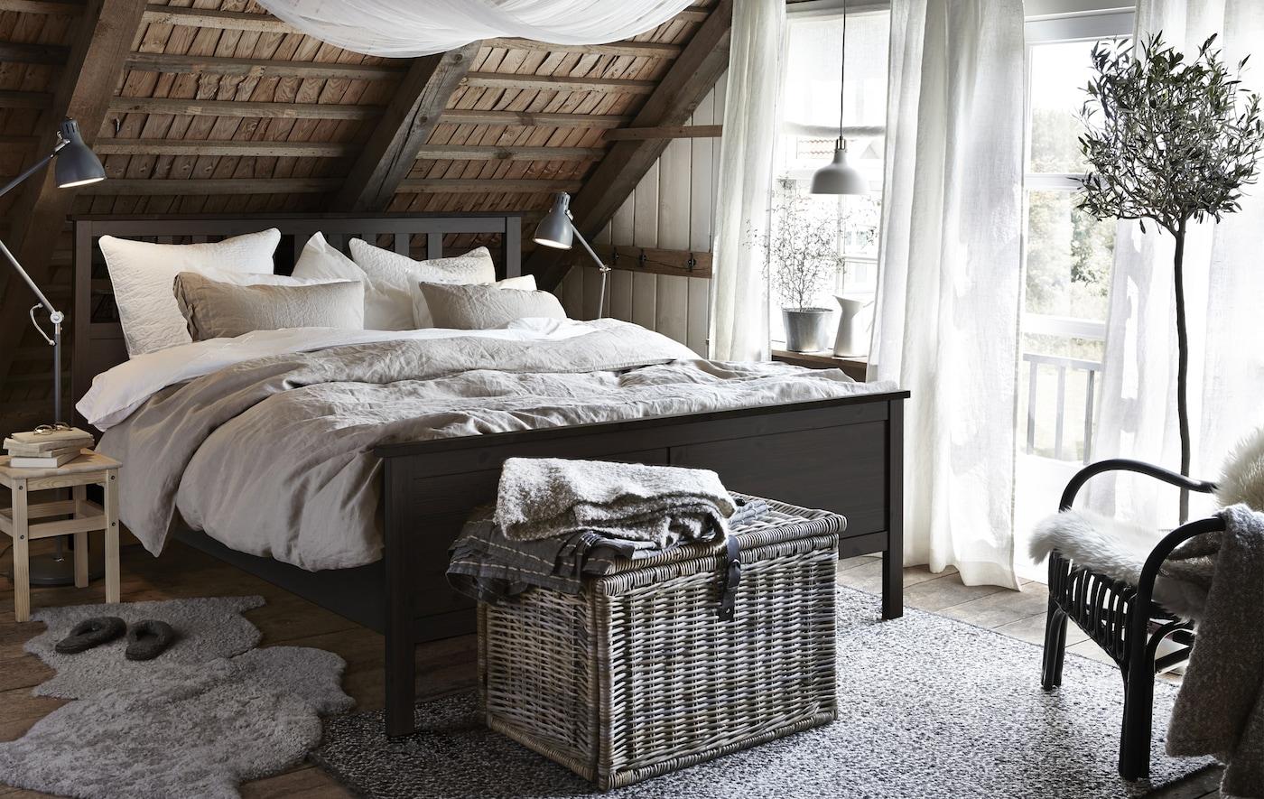 Chambres à coucher rustique avec cadre de lit HEMNES noir-brun, panier en wicker, peaux de mouton posées sur le sol et plafond en sous-pente lambrissé.