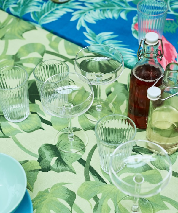 Champagne glasses and drinking glasses, with glass jars filled with drink on a table covered with green leaf-print fabric.