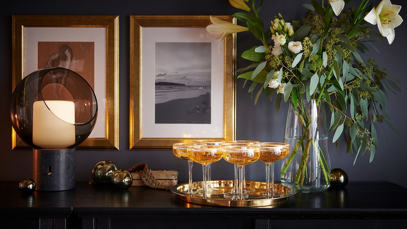 Champagne glasses on a tray, in front of a flower arrangement in a glass vase and two gold-framed pictures on the far wall.