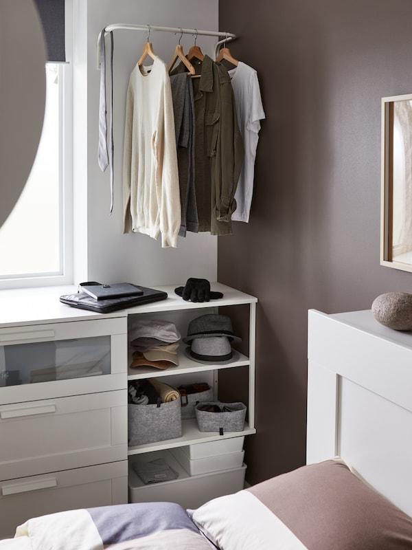 Chapeaux et accessoires rangés sur une étagère blanche, t-shirts suspendus à un porte-vêtements fixé au mur.