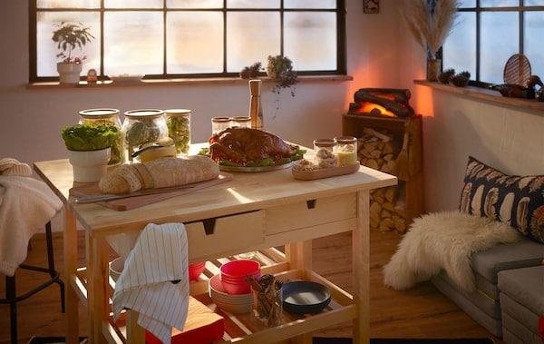 Chata s malým slávnostným bufetom prestretým na dvoch kuchynských vozíkoch a falošným krbom v rohu.