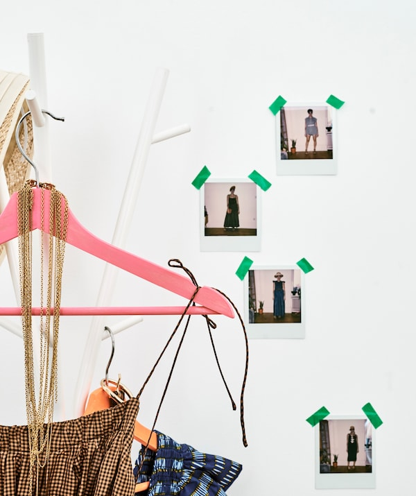 Checked summer dresses on colorful hangers hang on a coat stand by a wall taped with photos of a woman in different outfits.