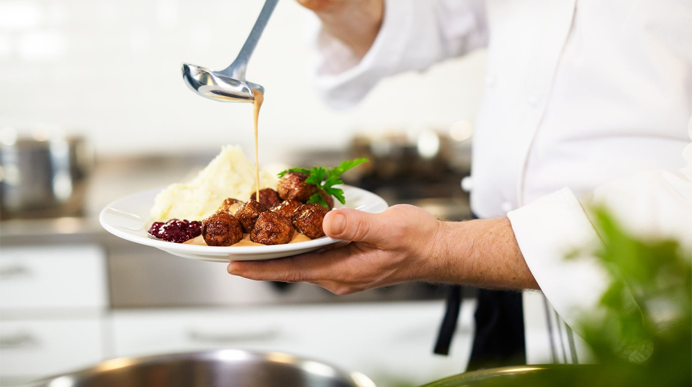 Chef serving meatballs with mashed potato, lingonberry jam and gravy.