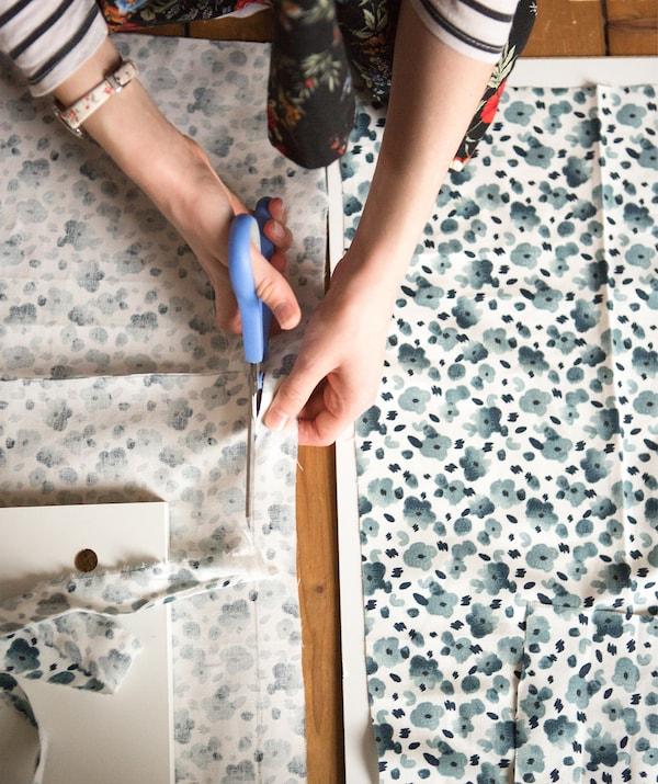 Человек разрезает ткань с синим цветочным узором.