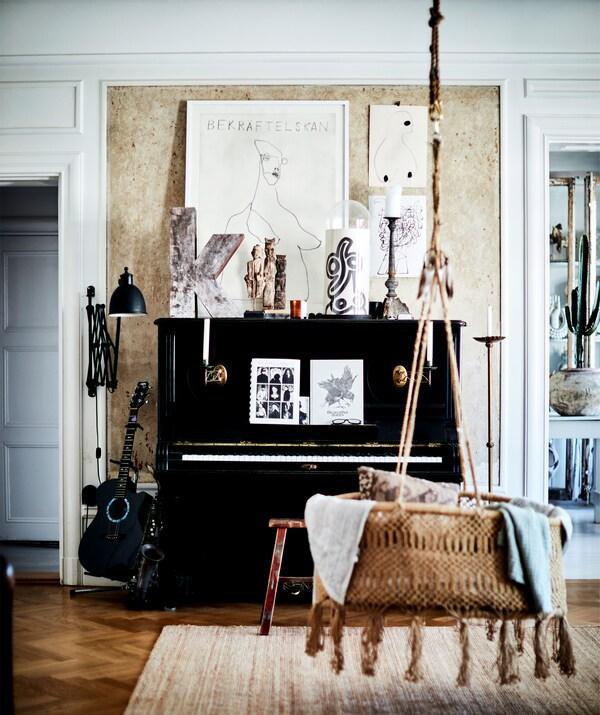Черное фортепиано и подвесное сиденье из ротанга в комнате с деревянным полом.