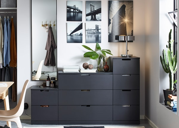 Chest of drawers NORDLI in black in a grey bedroom.