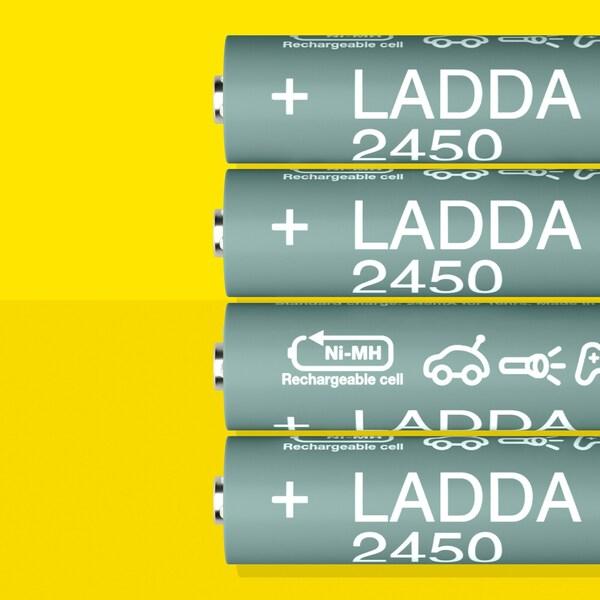 Четыре аккумуляторные батарейки ЛАДДА, HR6 AA емкостью 2450 мA*ч, лежат в ряд на желтой поверхности.