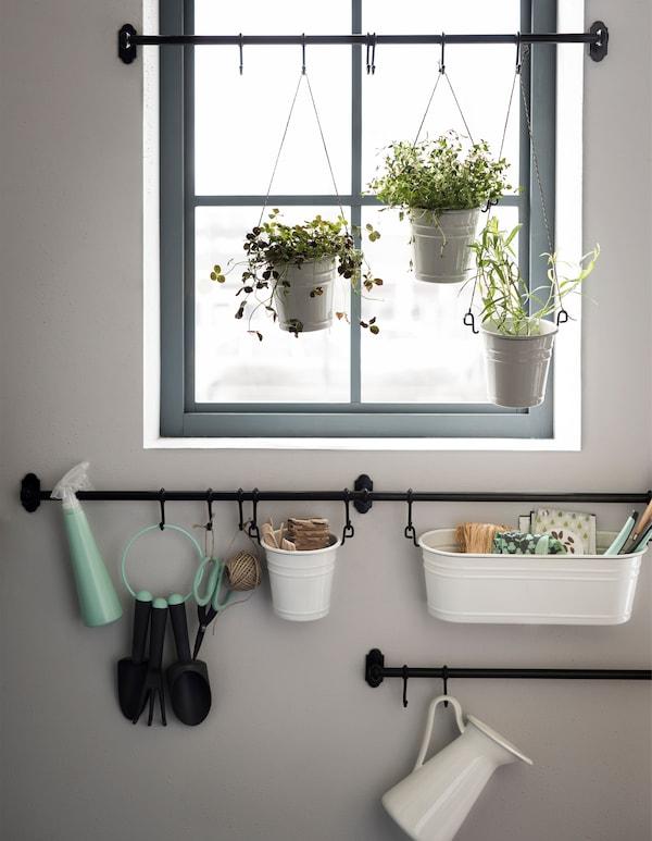 Chi è appassionato di giardinaggio può realizzare un angolo dedicato al verde fissando dei binari vicino alla finestra. Gli scolaposate possono essere usati come vasi da appendere ad altezze diverse con una corda, mentre gli attrezzi trovano spazio nel portacondimenti appeso con i ganci - IKEA