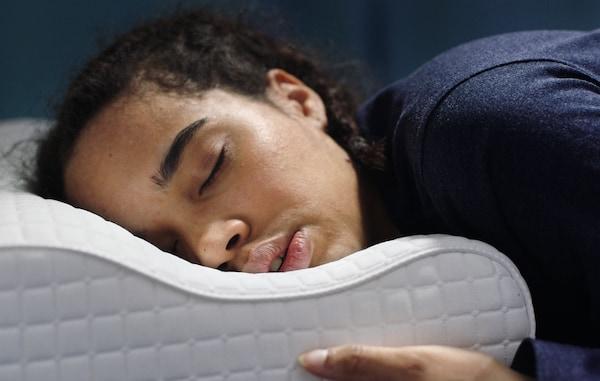 chica durmiendo en almohada cervical ergonómica