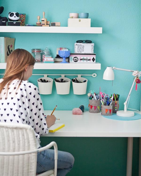 Chica joven sentada en un escritorio con estantes, portalápices y rieles.
