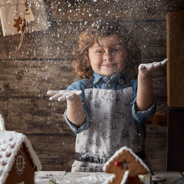 Child in kitchen making a gingerbread house