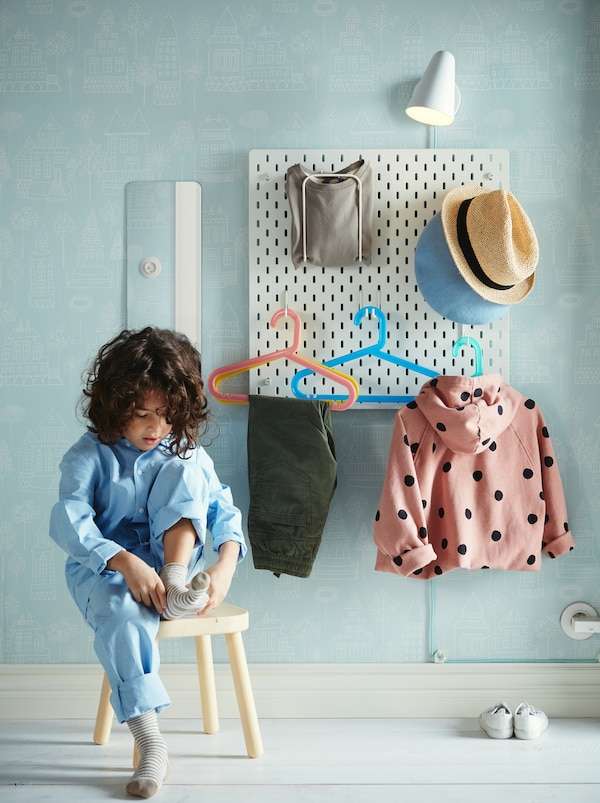 Child putting socks on, seated on a stool. On the wall behind hangs a SKÅDIS pegboard, holding various clothing items.