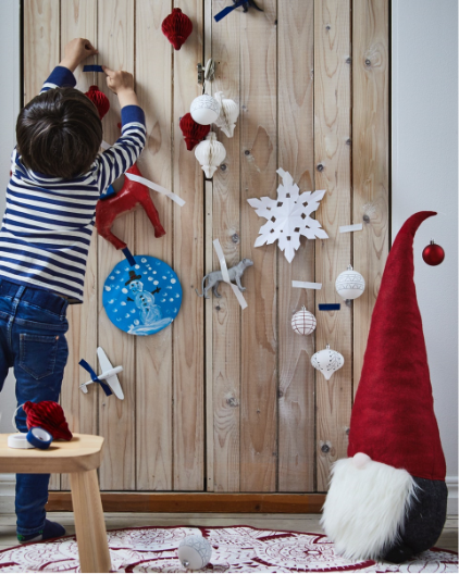 Child putting up Father Christmas-inspired decorations