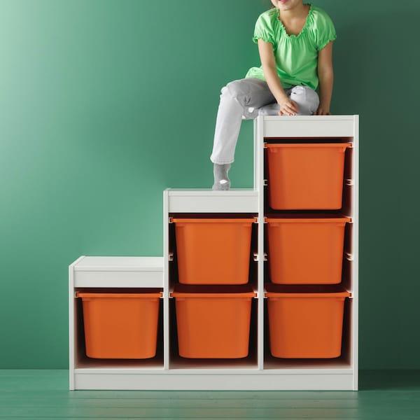 Child sitting on top of TROFAST storage system