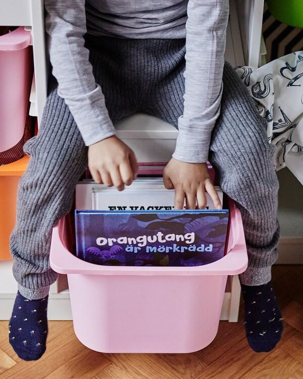 Child stores his books in the TROFAST storage bin.