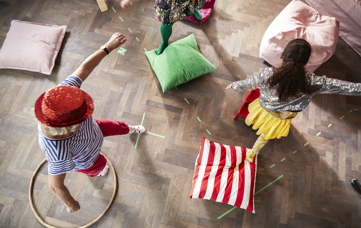 Children and adults playing a game with cushions on the floor.