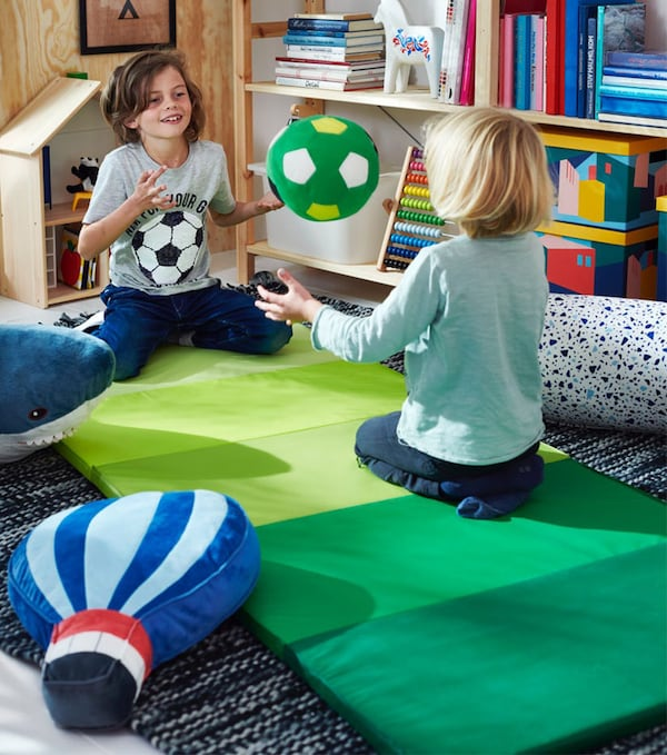 Children playing on the PLUFSIG mat - IKEA