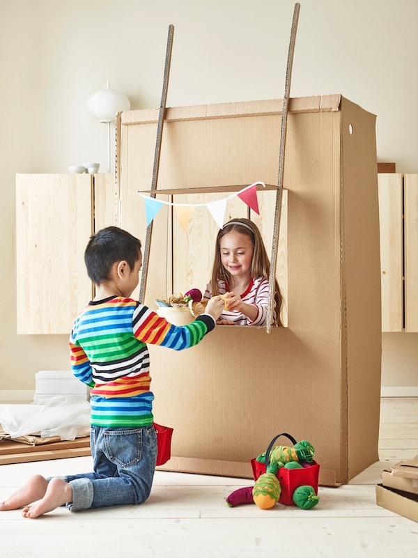 Children playing with a cardboard market stall.
