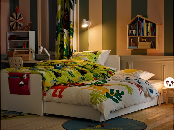 Children's room in an evening setting with a white bed frame with a rolled out underbed with bed textiles in animal prints.
