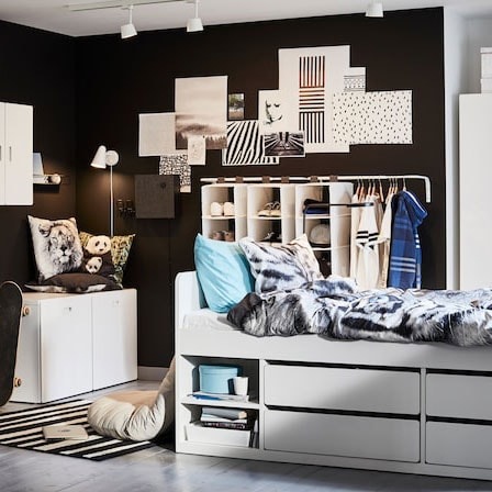 Children's room in white, blue and black with a white bed frame, tiger-patterned quilt cover and pillowcase and blue details.