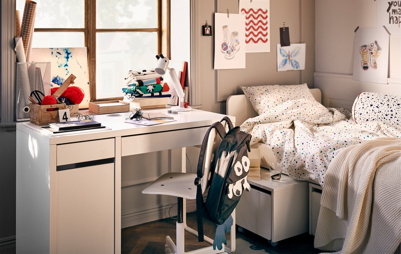 Children's room interior with bed, wall art and a workspace consisting of a MICKE desk, swivel chair and a KRUX lamp.