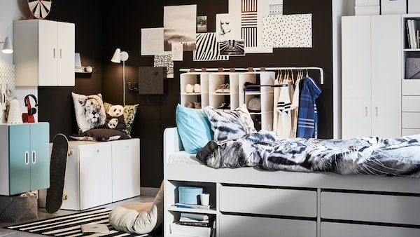 Children's room with a bed with storage, bedding and pillows, a closet beside it, a chest of drawers and a desk and chairs.