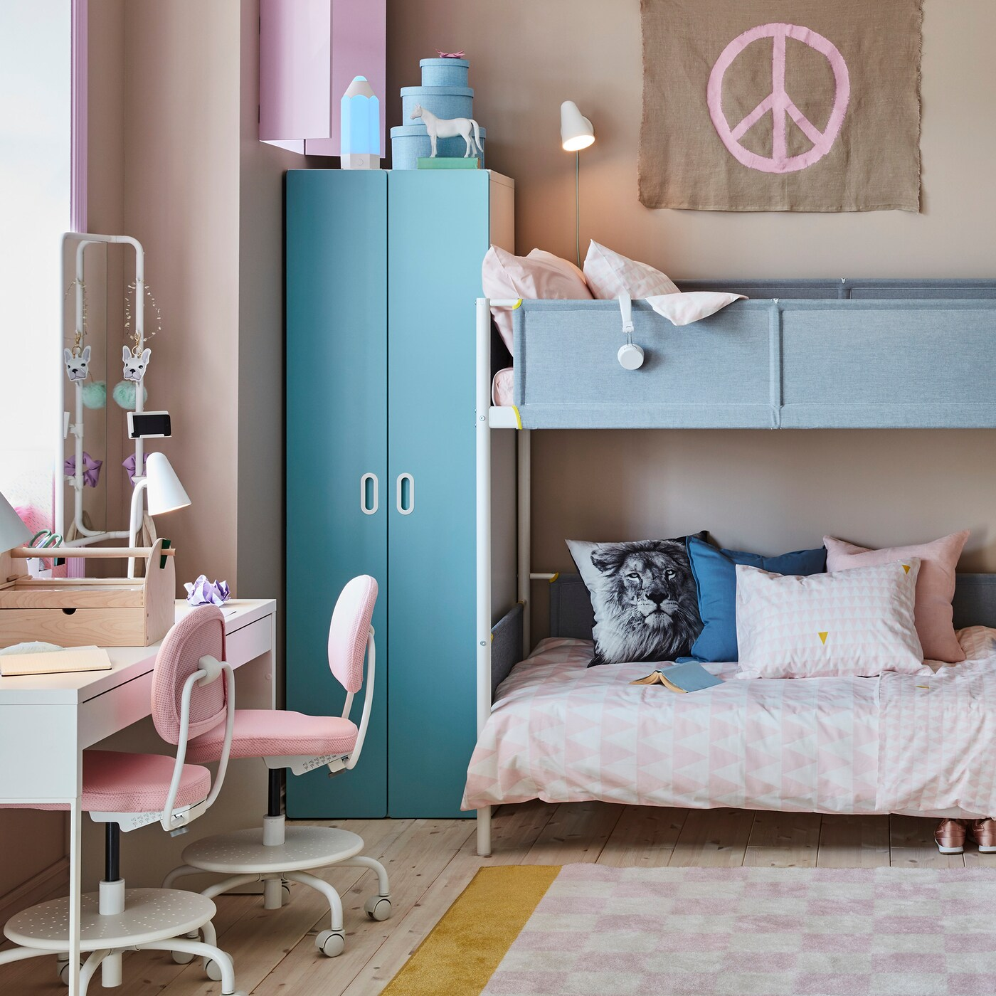 Children's room with a bunk bed with bedding and pillows, a closet beside it, a chest of drawers and a desk and chairs.