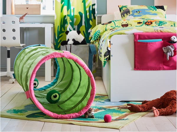 Children's room with a green play tunnel that's placed on a jungle-patterned rug. Soft toys inside and outside the tunnel.