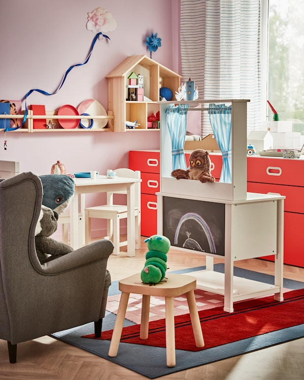 Children's room with a play kitchen that works as a puppet theatre, soft toys on an armchair and stool resembles an audience.