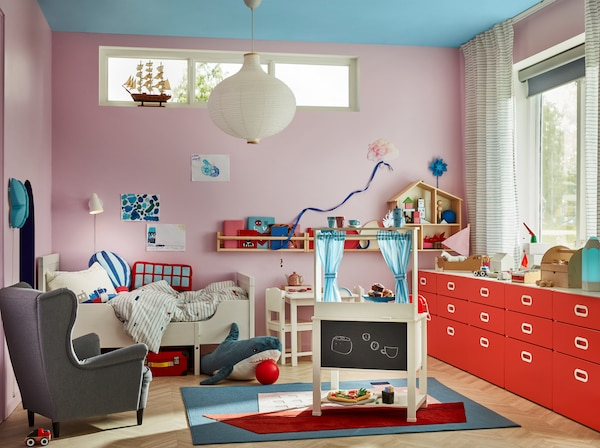 Children's room with a play kitchen with blue curtains and a blackboard, a children's armchair and a rug with a boat pattern.
