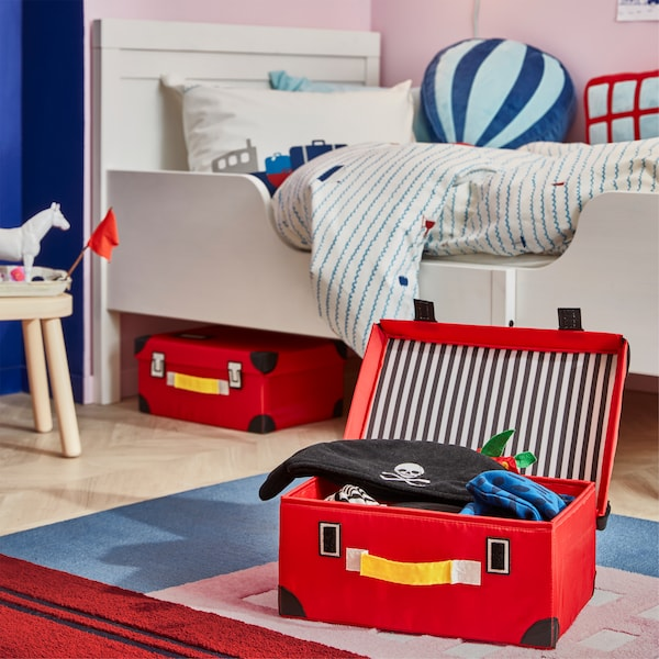 Children's room with a rug with a boat print, and placed on it is an open red FLYTTBAR trunk with pirate clothes inside.