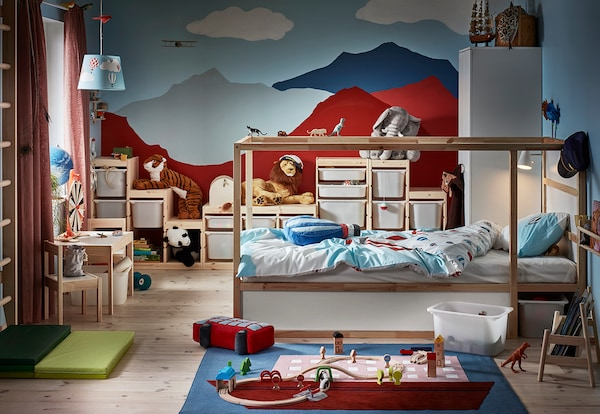 Children's room with KURA bed, TROFAST storage combination on the wall and a play area with LILLABO on the floor.