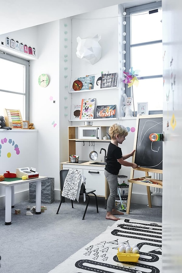 Children's room with toy kitchen, drawing board and play mat