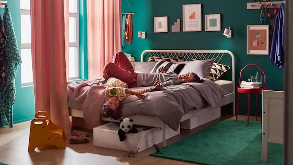 Chlapec s tatínkem leží na posteli v ložnici.