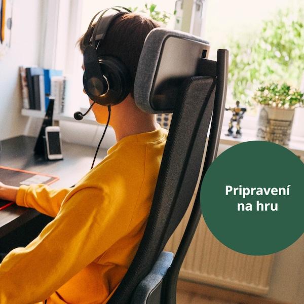 Chlapec sedí v čiernej kancelárskej stoličke JÄRVFJÄLLET so slúchadlami na ušiach a hraje počítačovú hru.