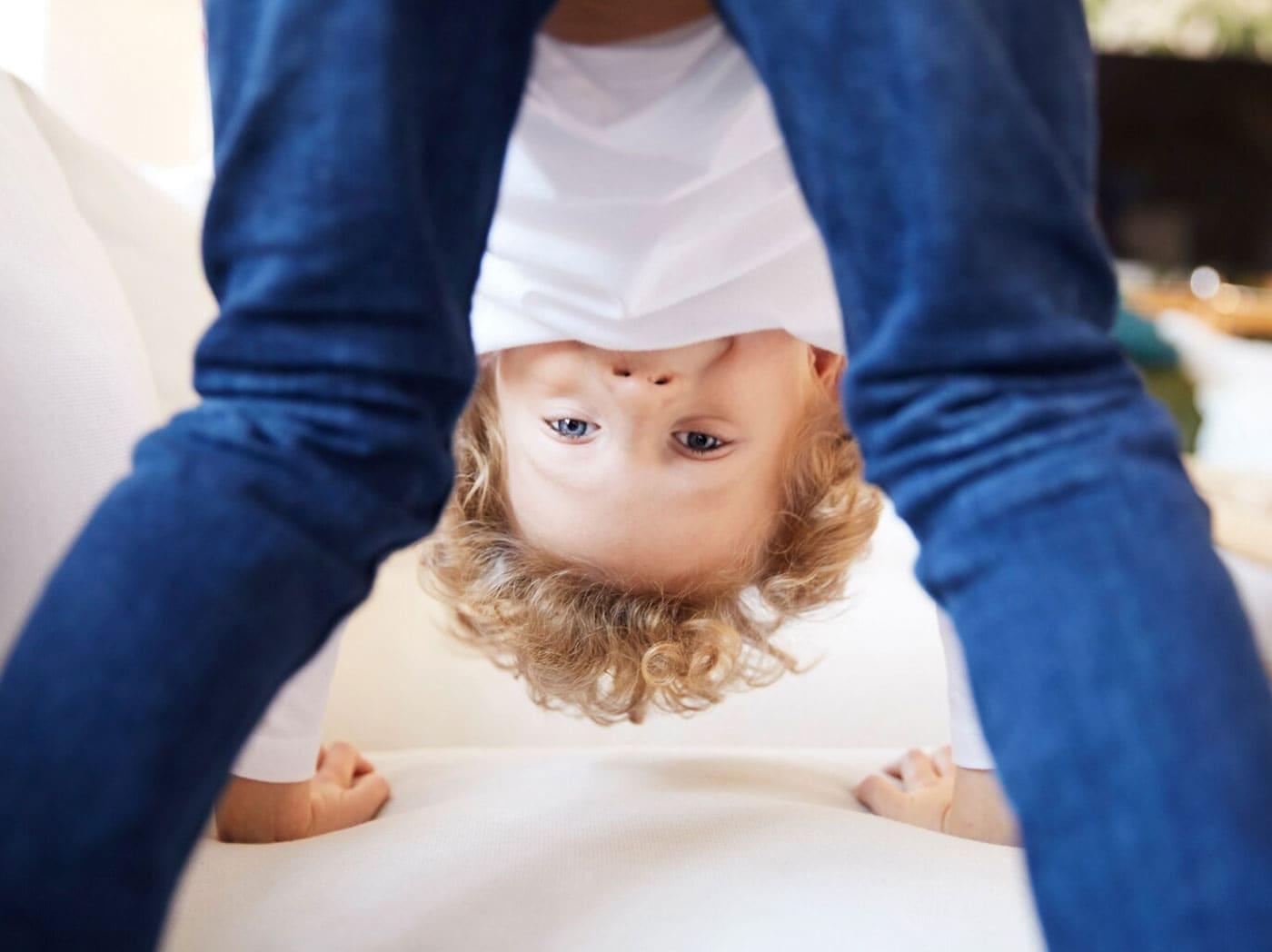 Chlapec stojící na všech čtyřech s hlavou mezi nohama na bílém gauči při hraní, symbolizující bezpečnost výrobků v IKEA.