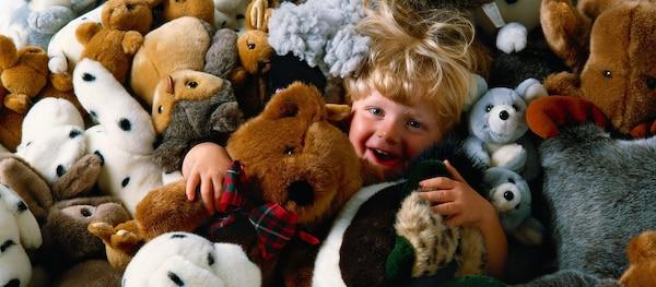 Chlapeček hrající se mezi plyšovými hračkami.