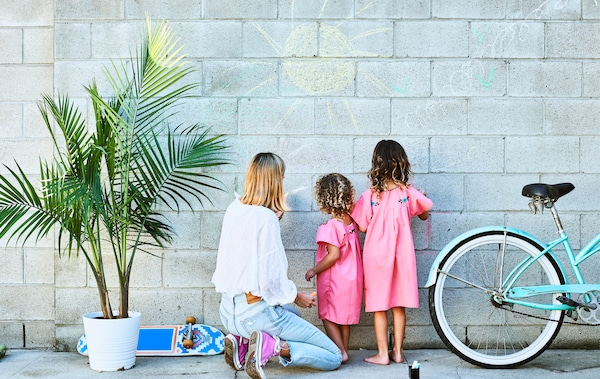 Chloé and her daughters drawing in chalk on a grey brick wall, with a pot plant and blue bike.