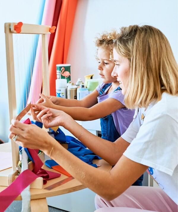 Chloé e a filha a tecer tiras de tecido num tear de madeira.